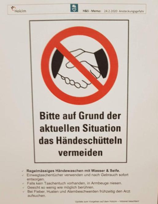 """""""Debido a la situación actual, evite darse la mano"""", dice un afiche colgado frente a la entrada de la planta de cemento Holcim en Untervaz GR. Imagen:Leser-Reporter"""